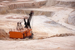 Open mine and excavator. Excavator digging out raw materials in opencast mine with copy space Royalty Free Stock Photo