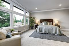Open modern bedroom interior with large windows and grey walls royalty free stock photos