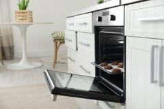 Open moderne oven met dienblad van gebakken koekjes royalty-vrije stock foto's