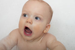 Open-mouthed baby boy is taking a bath in a soap foam.  Stock Photo