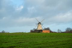 In the open nature in a field stands a windmill royalty free stock images