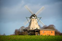 In the open nature in a field stands a windmill stock image