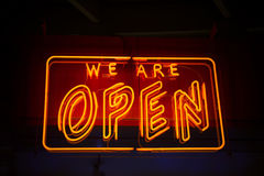 Open neon sign against dark background showing open for business Stock Image