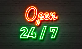 Open 24/7 neon sign on brick wall background. Stock Photo