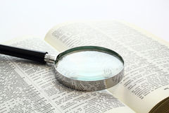 Open for new perspectives. Magnification glass over a opened book Stock Photo