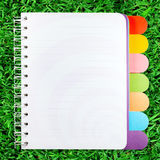 Open note book. On green grass background Royalty Free Stock Photo