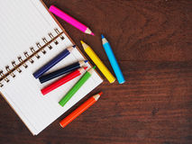 Open note book and color pencil on wooden background Royalty Free Stock Photos