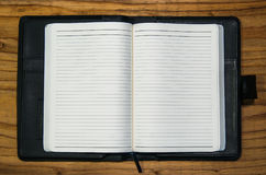 Open note book diary empty pages with black leather case. On wooden table Royalty Free Stock Photos