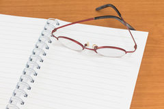 Open note book  with glasses. On wooden table Stock Photo