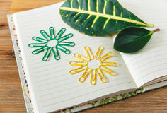 Open note book page,colored clips and green leaf.wooden background.selective focus. Stock Photo