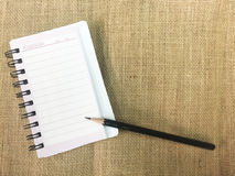 Open note book and pencil on sackcloth Royalty Free Stock Photos