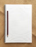 Open note book and pencil on sackcloth Stock Photography