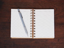 Open note book and pencil on wooden background Royalty Free Stock Image