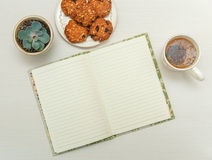 Open note book with tea,cookies,plant.white wooden table. Stock Photo