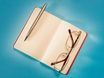 Open note, pen and eyeglasses on blue paper top view stock images
