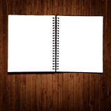 Open notebook. Black, open notebook on a wood background Royalty Free Stock Photo