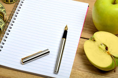 Open notebook with apple fruit Stock Photo