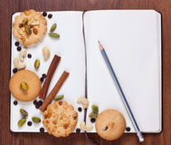Open notebook. Assorted cookies on blank notebook shot from above Stock Images