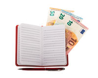 Open notebook with ballpoint pen and euro banknotes Royalty Free Stock Image