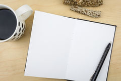 Open notebook with black pen and a cup of coffee Royalty Free Stock Photo
