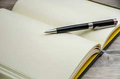 An open notebook and a black pen on it royalty free stock photo