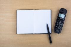 Open notebook and black phone on wooden texture Stock Photos