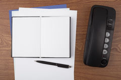 Open notebook and black phone on wooden texture Royalty Free Stock Image