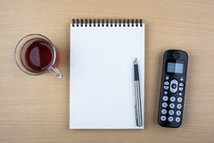 Open notebook and black phone on wooden texture Royalty Free Stock Images