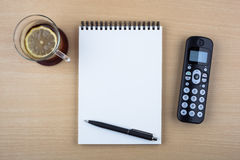 Open notebook and black phone on wooden texture Stock Photography