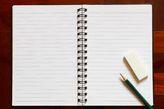 Open notebook with blank page and pencil and eraser. Wooden floo Stock Photos