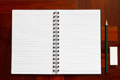 Open notebook with blank page and pencil and eraser. Wooden floo Stock Images