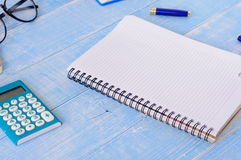 Open notebook with blank pages with calculator, pen and glasses Royalty Free Stock Photo