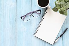 Open notebook with blank pages, coffee cup and eyeglasses on wooden desk table, top view or flat lay with copy space. Still life, business, planning or working stock images