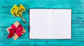 Open notebook with blank pages, gift box with ribbon and flowers. Royalty Free Stock Photography
