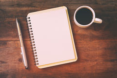 Open notebook with blank pages next to cup of coffee. Top view image of open notebook with blank pages next to cup of coffee on wooden table. ready for adding royalty free stock image