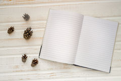Open notebook with blank pages, next to pine cones over wooden t Royalty Free Stock Photography