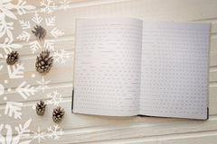 Open notebook with blank pages, next to pine cones over wooden t Royalty Free Stock Photos