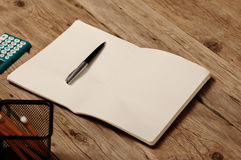 Open notebook with blank pages, pen and calculator Stock Images