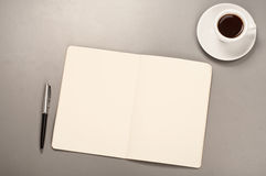 Open notebook with blank pages with a pen and coffee cup Stock Photo