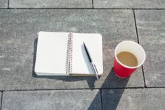 Open notebook with blank pages, pen and Cup of coffee on gray paving slab. Top view, stock photos