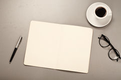 Open notebook with blank pages with a pen, glasses, coffee Stock Images