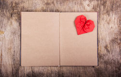 Open notebook with blank pages and Valentine origami. Red origami heart on a clean page. The concept of Valentine`s Day. Stock Images