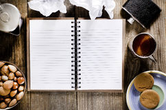 An open notebook with blank pages on wood table.Cup of tea,  hip Stock Image