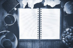 An open notebook with blank pages on wood table.Cup of tea,  hip flask,nuts and biscuits snack., Royalty Free Stock Photos