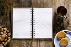 An open notebook with blank pages on wood table.Cup of tea, nuts Royalty Free Stock Image