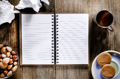 An open notebook with blank pages on wood table.Cup of tea, nuts and biscuits snack Stock Images