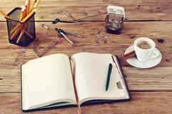 Open notebook with blank pages on wooden desk with a cup of coff Royalty Free Stock Image