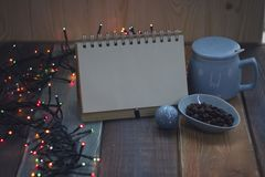 Open notebook, blue cup and coffee beans on Christmas tablen Stock Photos