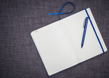 Open notebook with blue pen. Notebook opened to a blank page with blue pen, bookmark Royalty Free Stock Image