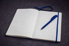 Open notebook with blue pen. Notebook opened to a blank page with blue pen, bookmark Royalty Free Stock Photography